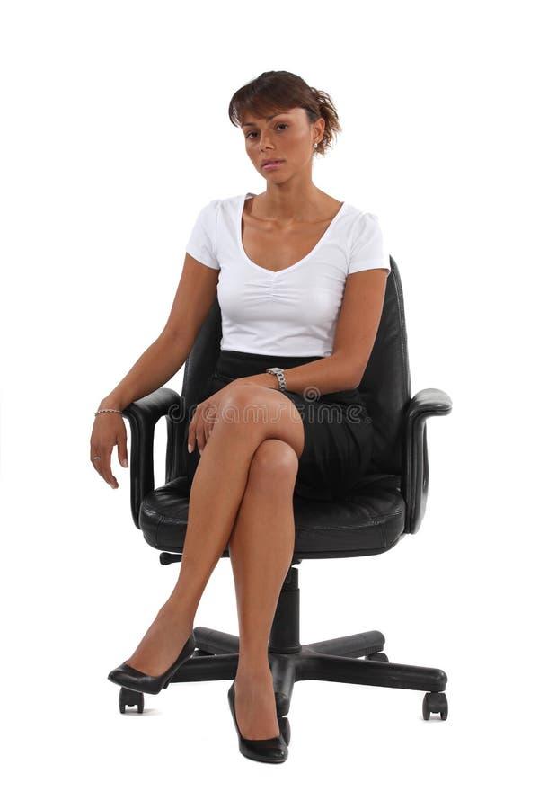 Donna di affari seduta nella sedia dell'ufficio immagini stock