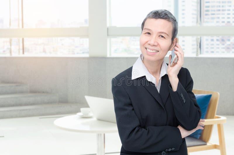 Donna di affari senior che lavora all'ufficio fotografie stock libere da diritti