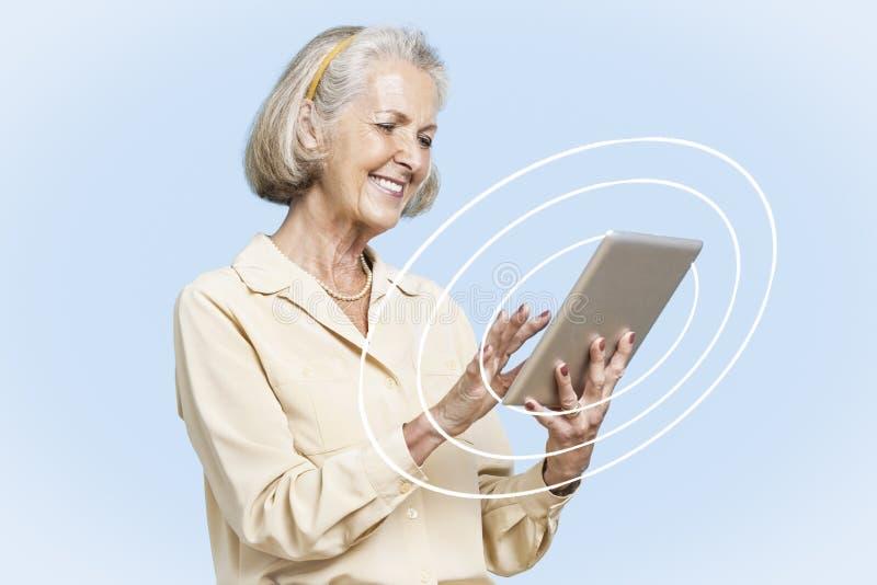 Donna di affari senior felice che per mezzo del PC della compressa contro il chiaro cielo blu fotografia stock libera da diritti