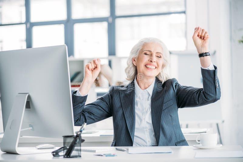 Donna di affari senior nell'usura convenzionale che si siede nel luogo di lavoro e che trionfa fotografie stock