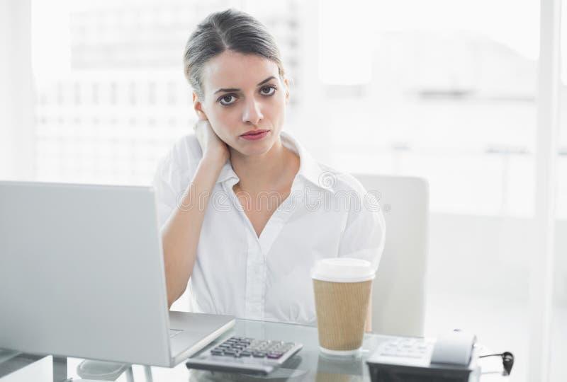Donna di affari seria calma che si siede al suo scrittorio fotografie stock libere da diritti