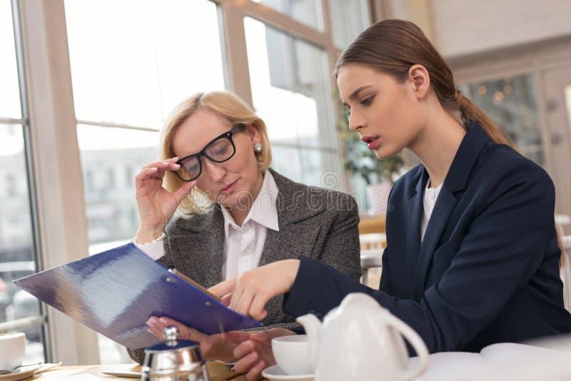 Donna di affari seria che discute le statistiche con il suo apprendista fotografia stock libera da diritti