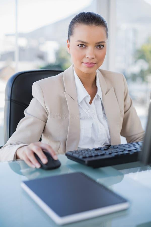 Donna di affari seria che lavora al computer che esamina macchina fotografica fotografia stock libera da diritti