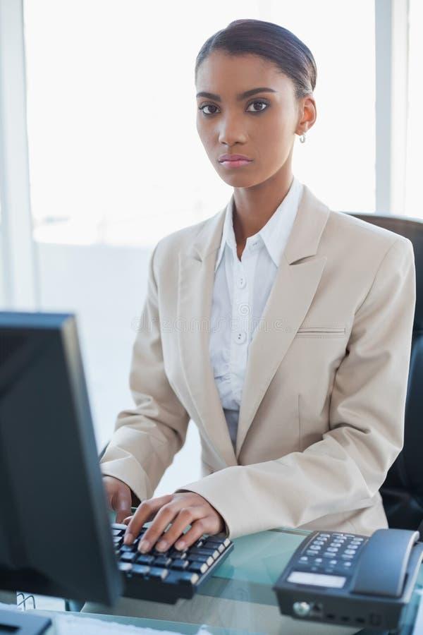 Donna di affari seria che lavora al suo computer fotografia stock libera da diritti