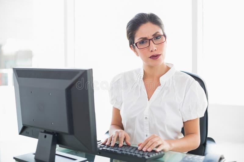 Donna di affari seria che lavora al suo scrittorio che esamina macchina fotografica immagini stock libere da diritti