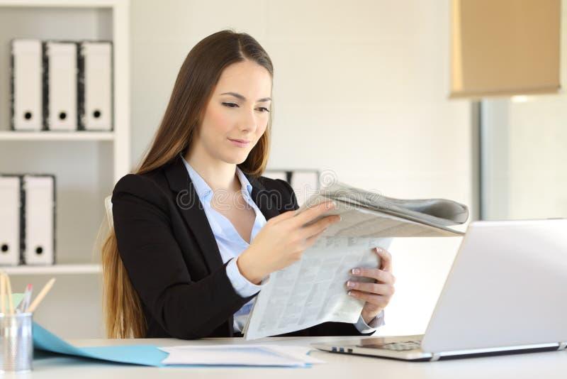 Donna di affari seria che legge un giornale all'ufficio fotografia stock