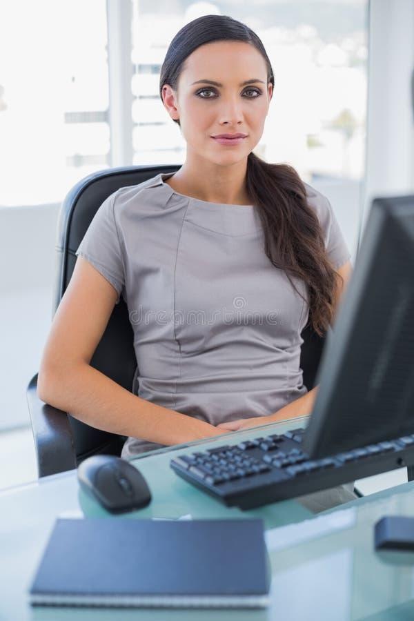 Donna di affari seria che si siede sulla sua poltrona girevole fotografie stock