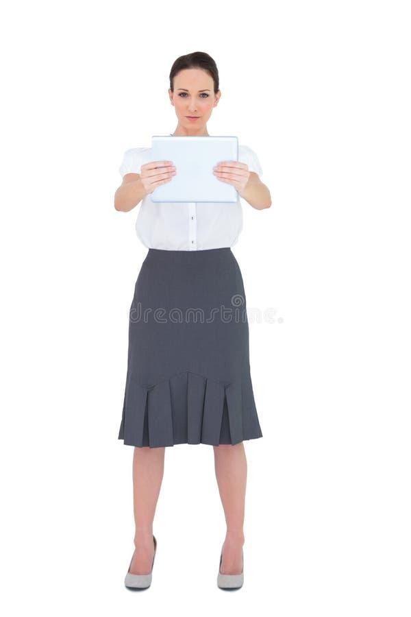 Donna di affari seria che tiene il suo pc della compressa fotografia stock