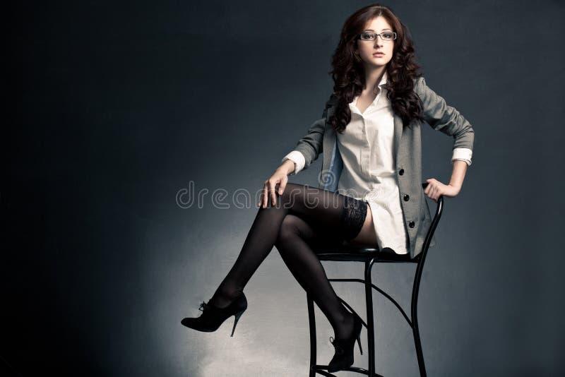 Donna di affari sessuale che si siede sulla presidenza fotografia stock