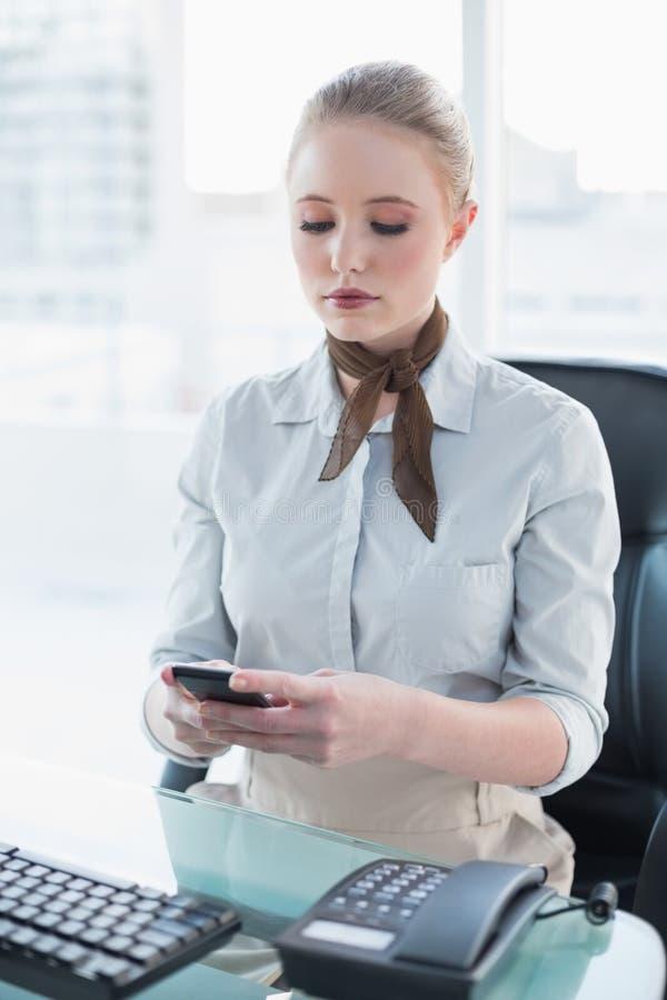 Donna di affari severa bionda che per mezzo dello smartphone fotografie stock