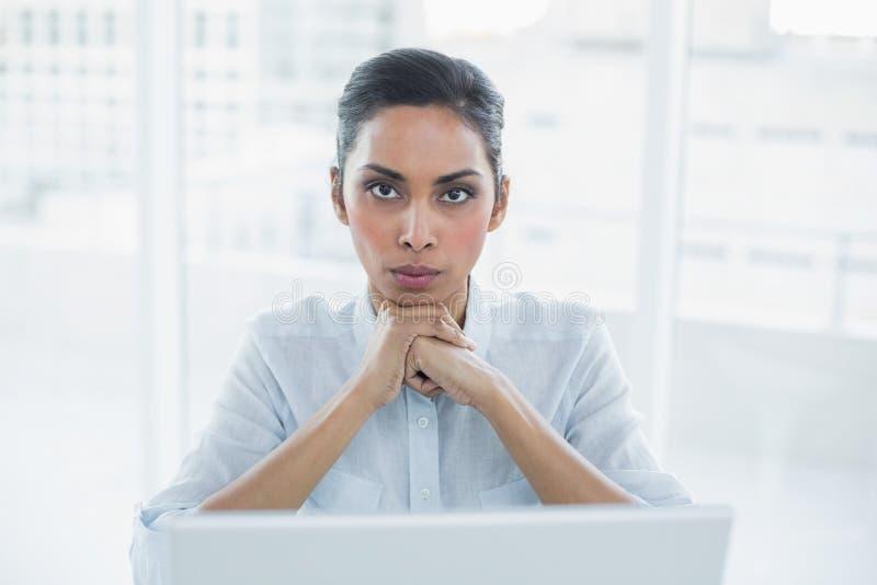 Donna di affari severa che si siede al suo scrittorio che esamina macchina fotografica immagine stock libera da diritti