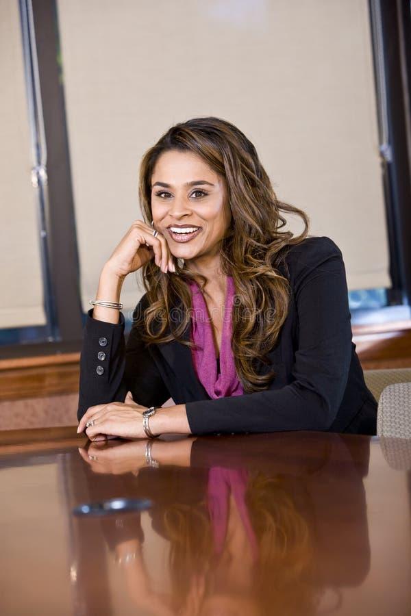 Donna di affari sicura che si siede nella sala del consiglio fotografia stock