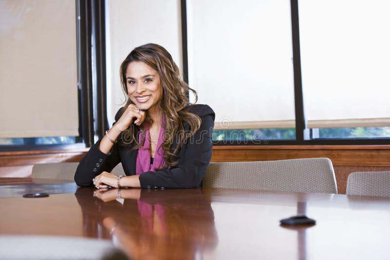 Donna di affari sicura che si siede nella sala del consiglio immagine stock libera da diritti