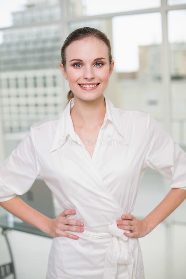 Donna di affari sicura che sorride alla macchina fotografica con le mani sulle anche immagini stock libere da diritti