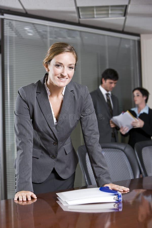 Donna di affari sicura, colleghi nella priorità bassa immagine stock libera da diritti