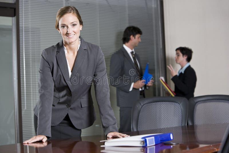 Donna di affari sicura, colleghi nella priorità bassa immagine stock