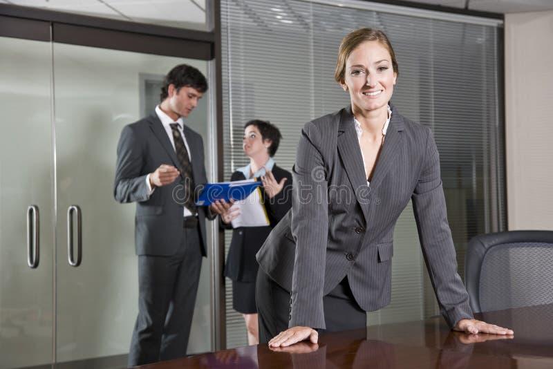 Donna di affari sicura, colleghi nella priorità bassa immagini stock