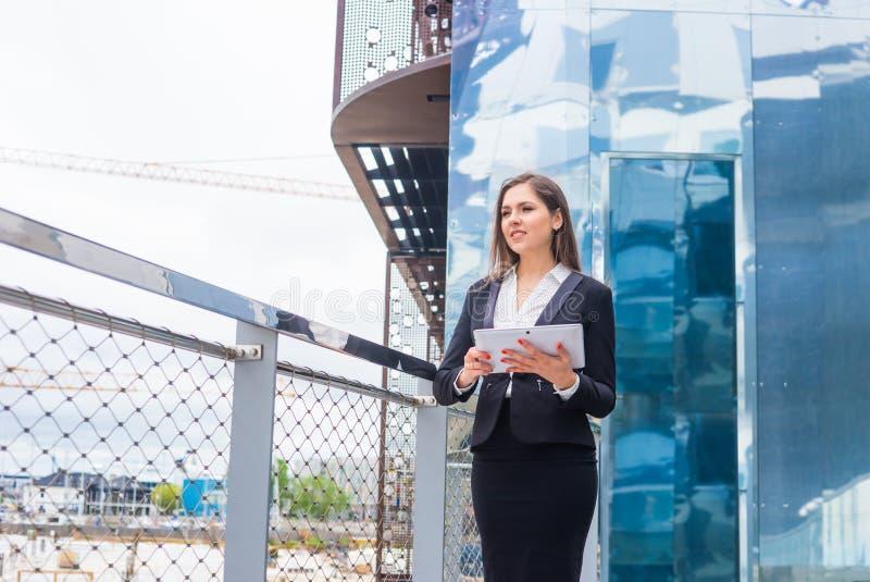 Donna di affari sicura davanti all'edificio per uffici moderno Concetto di affari, di attività bancarie, di società e del mercato fotografia stock
