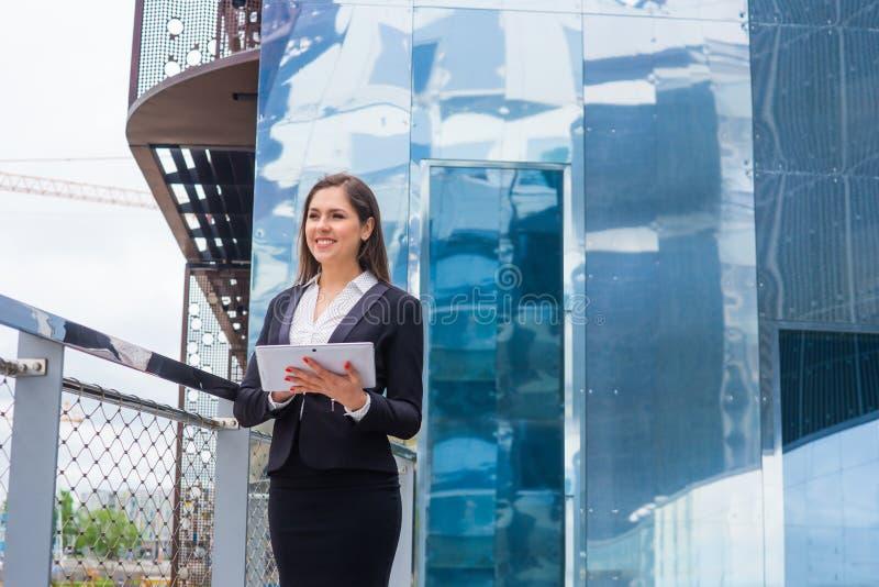Donna di affari sicura davanti all'edificio per uffici moderno Concetto di affari, di attività bancarie, di società e del mercato immagine stock