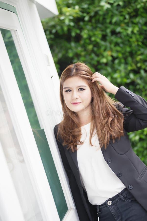 Donna di affari sicura dell'Asia giovane in vestito che si tiene per mano sui capelli fotografia stock libera da diritti