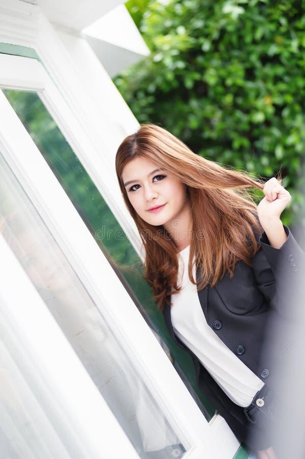 Donna di affari sicura dell'Asia giovane in vestito che si tiene per mano sui capelli fotografie stock libere da diritti