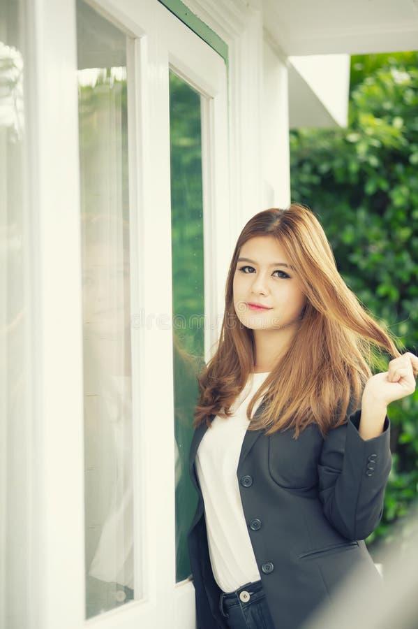 Donna di affari sicura dell'Asia giovane in vestito che si tiene per mano sui capelli immagini stock