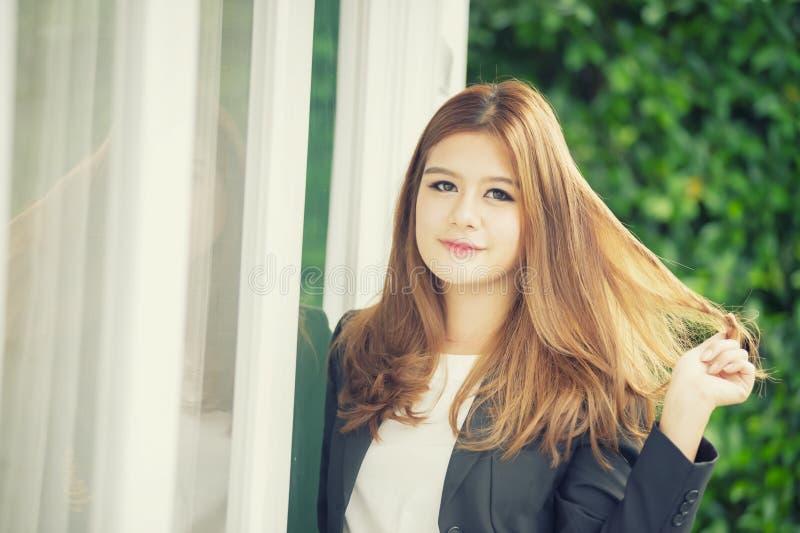 Donna di affari sicura dell'Asia giovane in vestito che si tiene per mano sui capelli fotografia stock