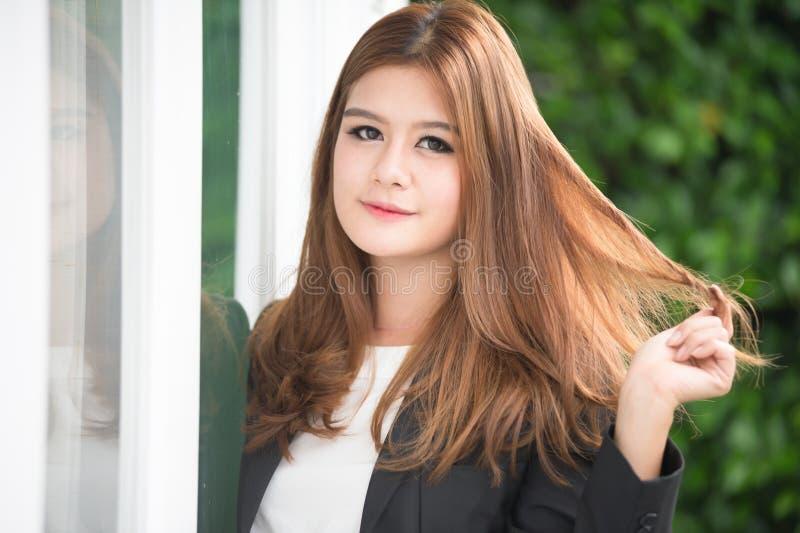 Donna di affari sicura dell'Asia giovane in vestito che si tiene per mano sui capelli immagine stock