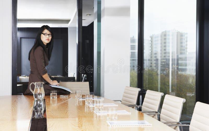 Donna di affari Sitting On Table in sala del consiglio immagini stock