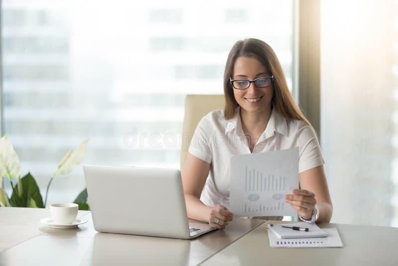 Donna di affari soddisfatta che rivede i risultati finanziari fotografia stock libera da diritti