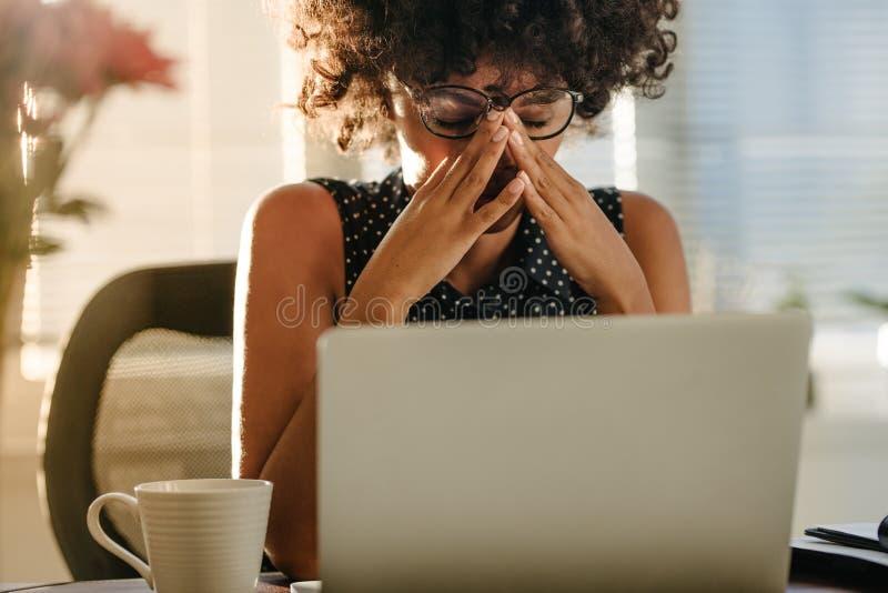 Donna di affari sollecitata che si siede allo scrittorio immagini stock