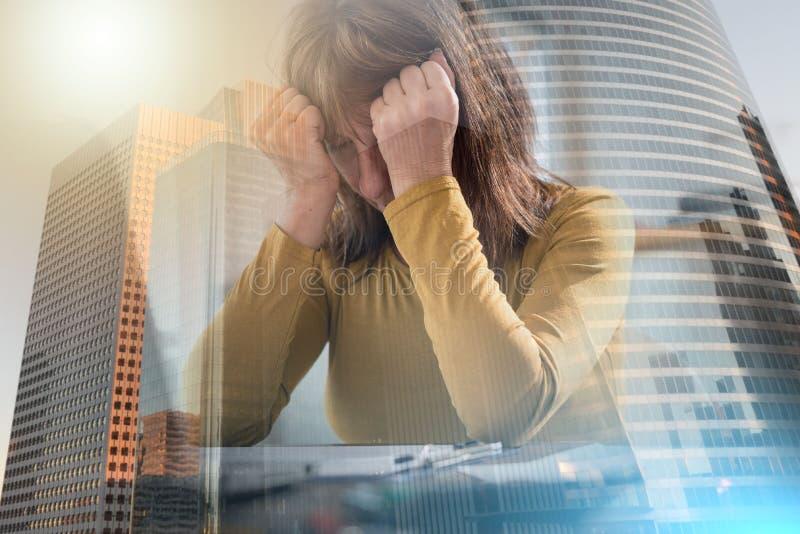 Donna di affari sollecitata che si siede nell'ufficio; esposizione multipla fotografia stock