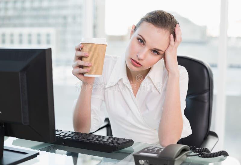Donna di affari sollecitata che tiene tazza eliminabile che esamina macchina fotografica immagine stock