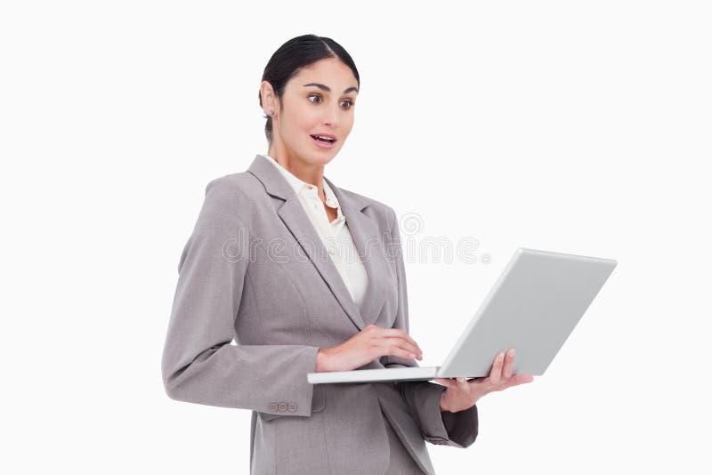 Donna di affari sorpresa che esamina il suo computer portatile fotografia stock