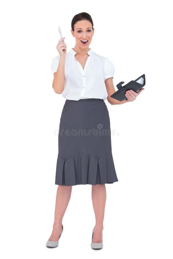 Donna di affari sorpresa che tiene il suo datebook fotografia stock libera da diritti