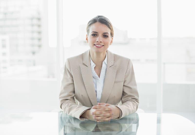 Donna di affari sorridente adorabile che si siede al suo scrittorio fotografia stock libera da diritti
