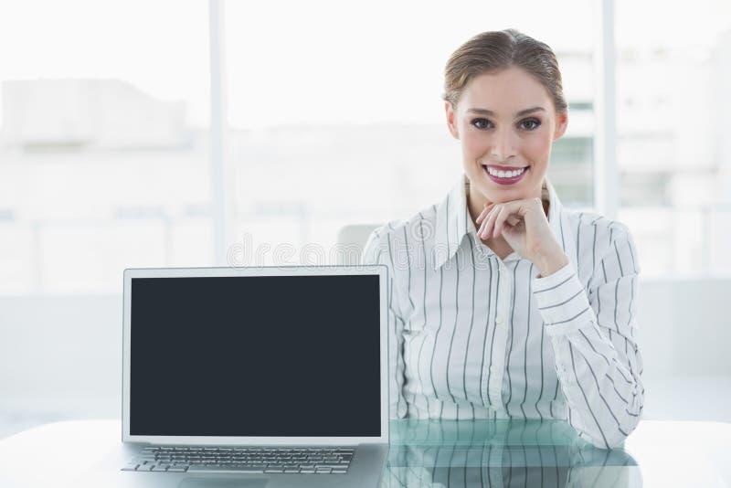 Donna di affari sorridente adorabile che si siede al suo scrittorio che mostra taccuino fotografia stock libera da diritti