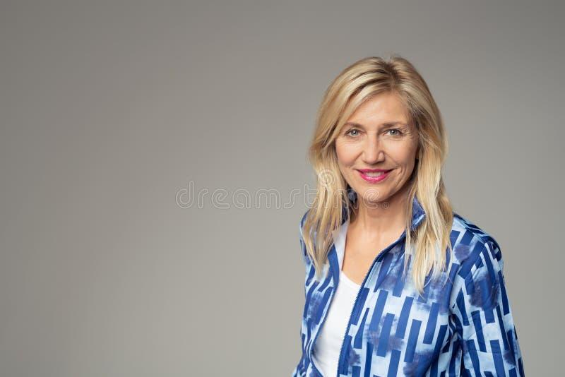 Donna di affari sorridente Against Gray con lo spazio della copia fotografie stock