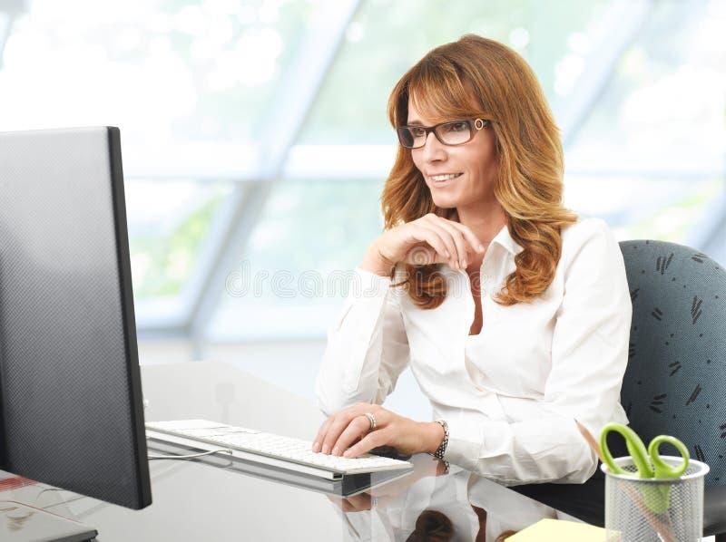 Donna di affari sorridente alla scrivania con un computer fotografia stock