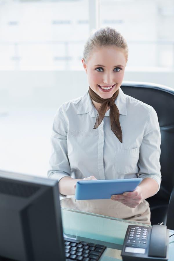 Donna di affari sorridente bionda che per mezzo della compressa fotografia stock libera da diritti