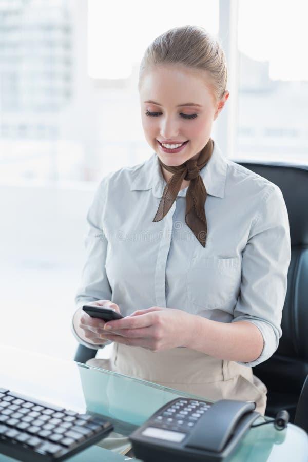 Donna di affari sorridente bionda che per mezzo dello smartphone fotografie stock libere da diritti