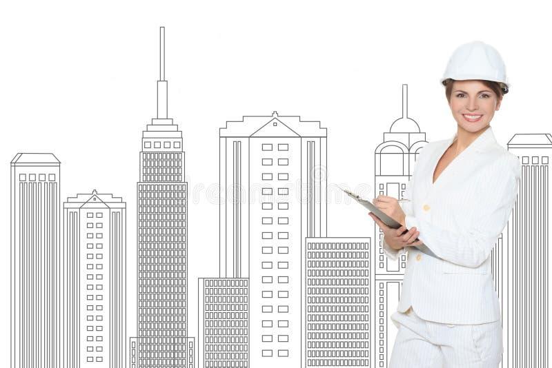 Donna di affari sorridente in casco che studia lo schizzo del centro futuro di affari fotografie stock