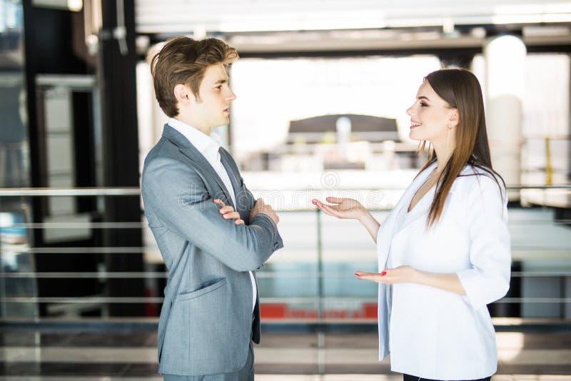 Donna di affari sorridente che dice qualcosa al suo collega nell'ufficio L'uomo di affari parla con la donna di affari in ufficio immagine stock