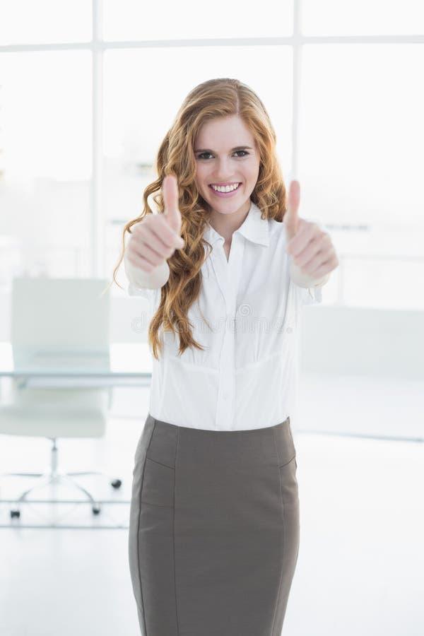 Donna di affari sorridente che gesturing i pollici su all'ufficio immagine stock
