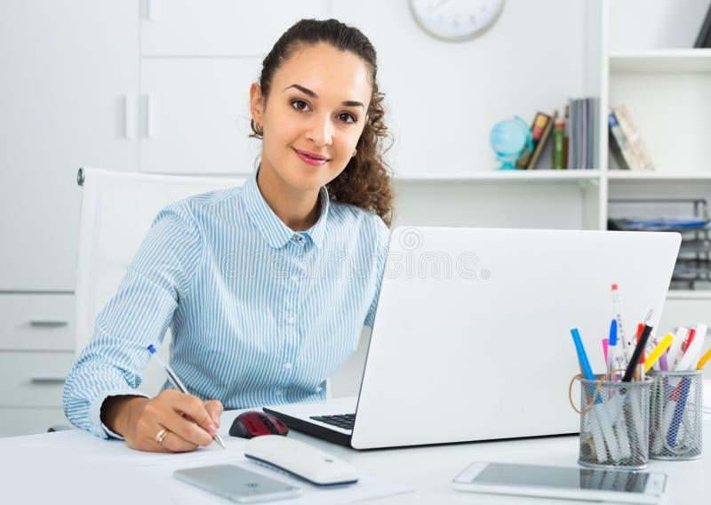 Donna di affari sorridente che lavora con i documenti in ufficio immagini stock