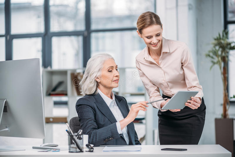 Donna di affari sorridente che mostra compressa digitale al collega senior che indica allo schermo immagine stock