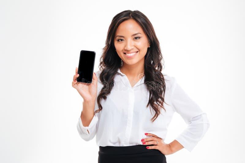 Donna di affari sorridente che mostra lo schermo in bianco dello smartphone fotografie stock