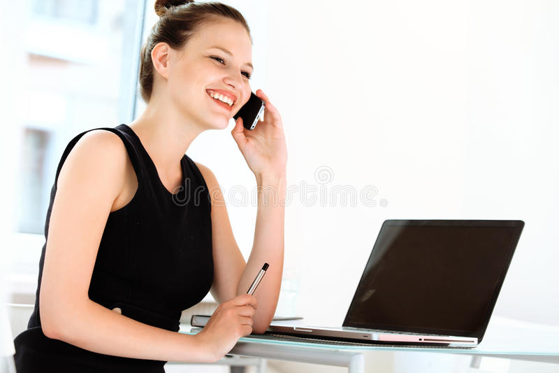 Donna di affari sorridente che parla sul telefono cellulare in un ufficio fotografie stock