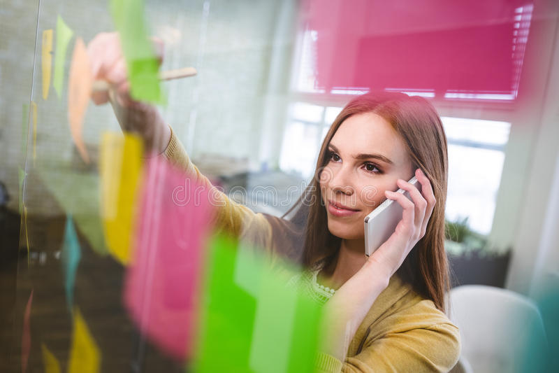 Donna di affari sorridente che parla sulla scrittura bianca del telefono sulle note appiccicose fotografia stock libera da diritti