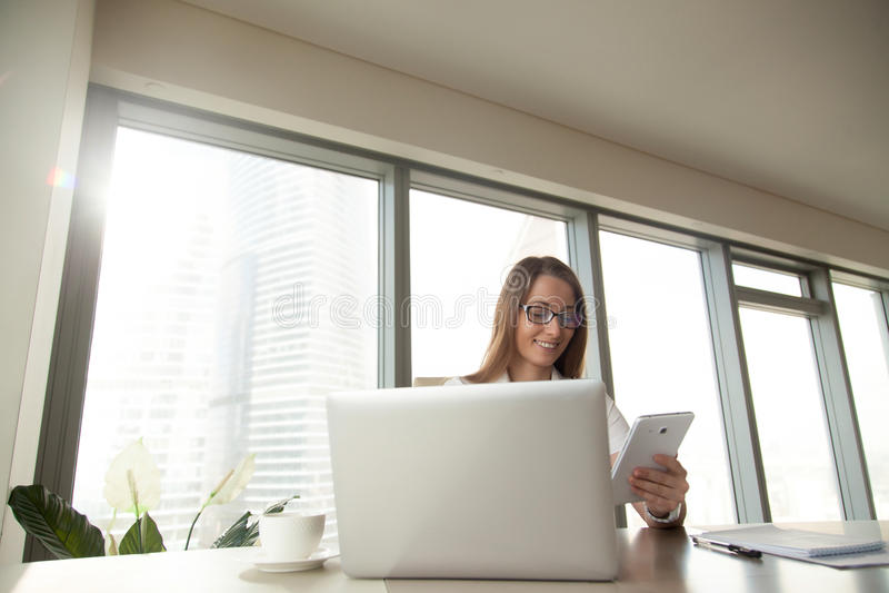 Donna di affari sorridente che per mezzo del computer della compressa che si siede nel luogo di lavoro fotografia stock